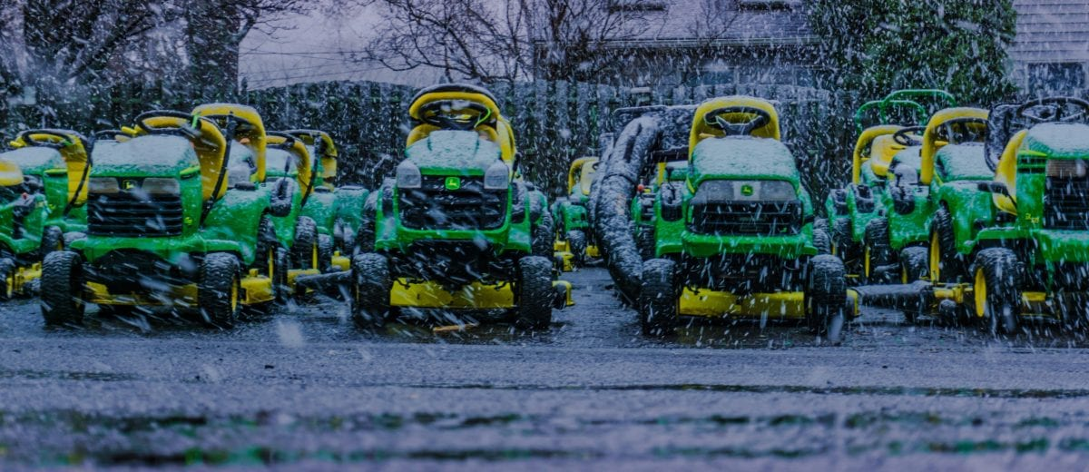 exterior photo of john deer tractors lined up outside as it snows